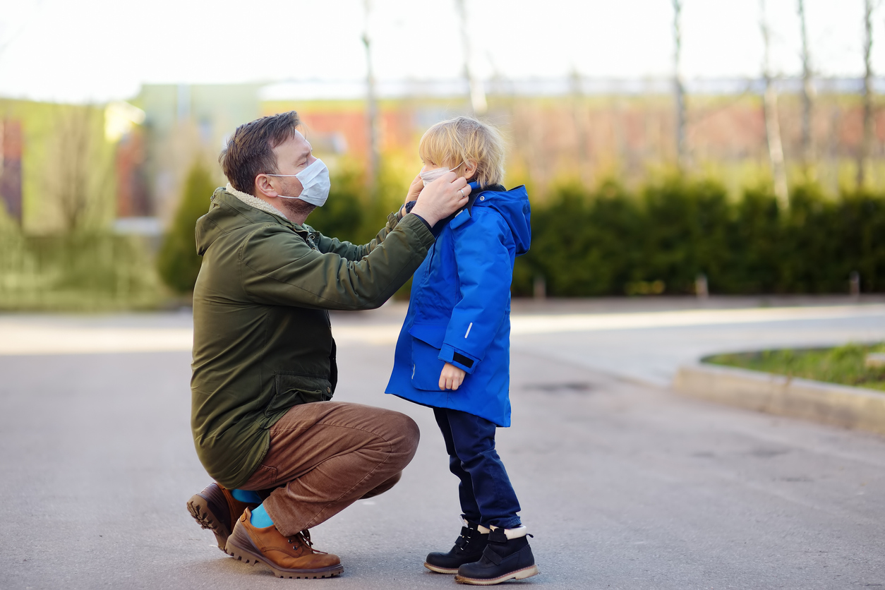 Mature man wearing a protective mask puts a face mask on a his son in airport, supermarket or other public place. Safety during COVID-19 outbreak. Epidemic of virus covid. Discussing the common covid-19 myths..