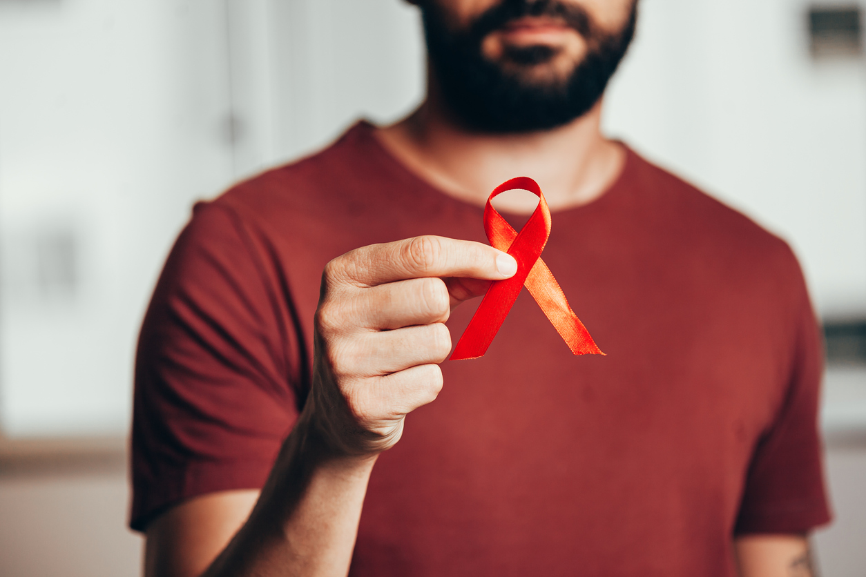 Man holding red ribbon for HIV illness awareness, 1 December World AIDS Day concept, highlighting the importance of education on HIV & AIDS.