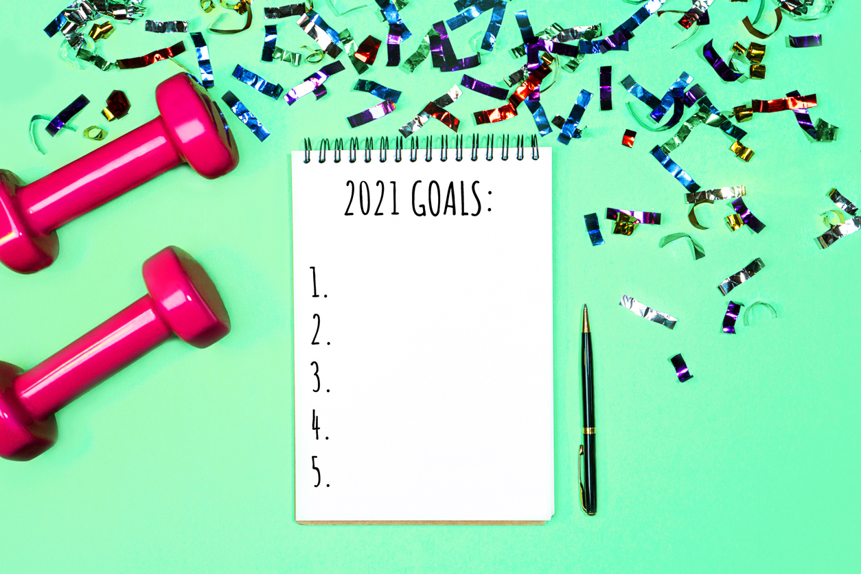 Goals list for New Year Holiday. Christmas sport set with dumbbells, notebook with pen and colorful confetti on on pastel mint green blue background. Flat lay, top view, copy space, highlighting health resolutions you should commit to in 2021.