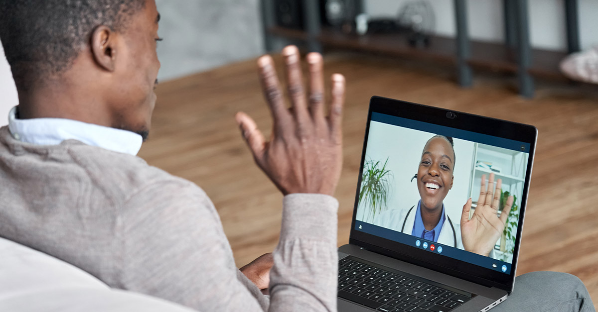 Friendly patient waving to smiling doctor during a virtual visit.