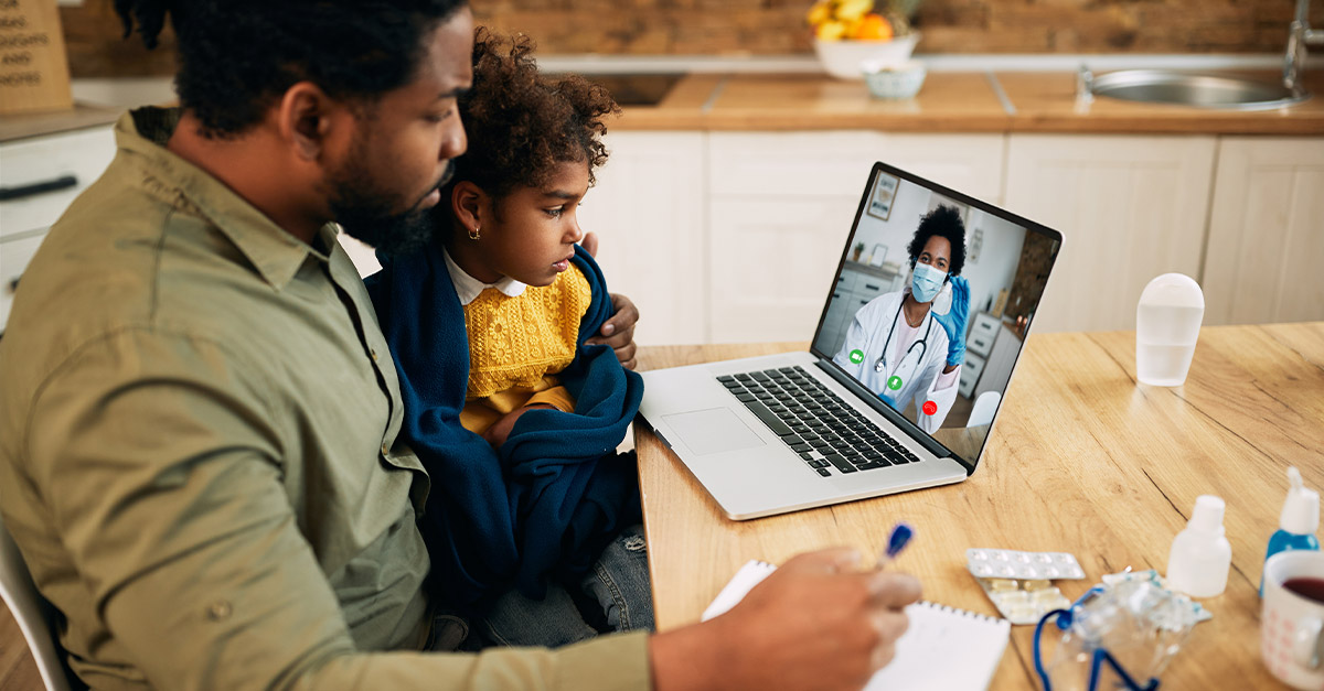 Father with sick son looking at doctor on screen for a telehealth appointment.